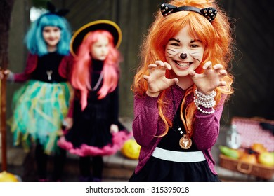 Frightening girl in Halloween costume looking at camera with two friends on background