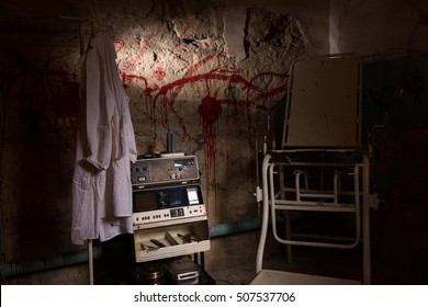 Frightful electrical shocking device near medical gown hanging on the hanger and scary chair with blood stained wall for concept about torture or scary Halloween theme