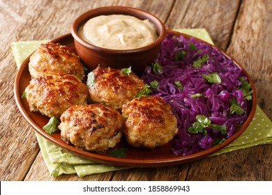 Frikadeller are Danish meatballs made with veal and pork with creamy sauce and stew red cabbage close up in the plate on the table. horizontal