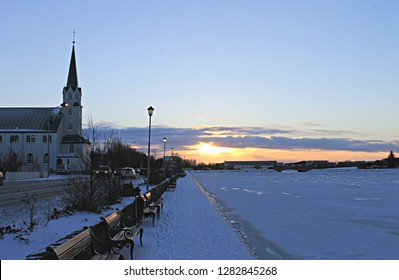Frikirkjan Lutheran church in profile with a line of wood benches set on a snowy promenade by an icy frozen lake Tjornin and pale blue sunset sky background, Reykjavik, Iceland capital