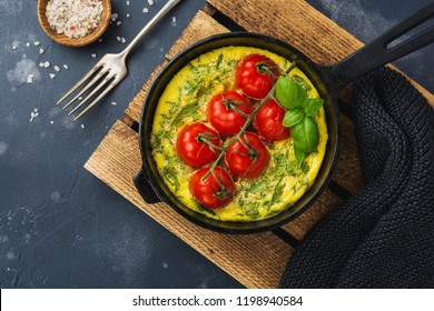 Frittata with arugula, potatoes and cherry tomatoes in iron pan on old stone table background. Top view.