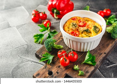 Frittata with broccoli ceramic form. Frittata with broccoli, sweet bell peppers and tomatoes in two ceramic forms for baking. Italian omelet with vegetables