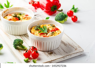 Frittata with broccoli in two ceramic forms. Frittata with broccoli, sweet bell peppers and tomatoes in two ceramic forms for baking. Italian omelet with vegetables