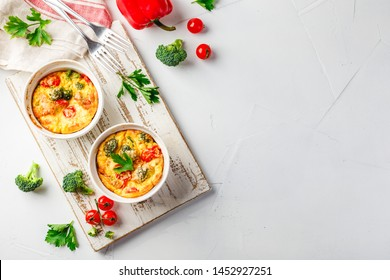 Frittata with broccoli in two ceramic forms. Frittata with broccoli, sweet bell peppers and tomatoes in two ceramic forms for baking. Italian omelet with vegetables. View from above