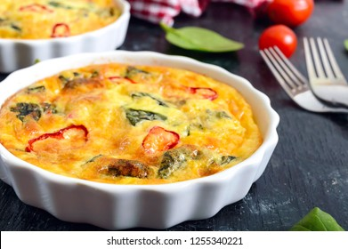 Frittata with fresh vegetables and spinach. Italian omelet in ceramic forms on a black background. Close up