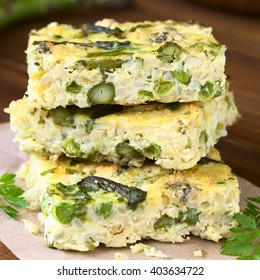 Frittata made of eggs, green asparagus, pea, blue cheese, parsley and brown rice, photographed on dark wood with natural light (Selective Focus, Focus on the front of the upper frittata)