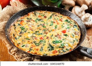Frittata made of eggs, mushrooms and spinach on a frying pan. Italian cuisine