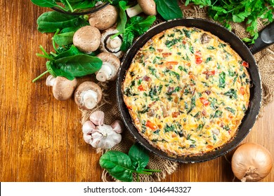 Frittata made of eggs, mushrooms and spinach on a frying pan. Italian cuisine. Top view
