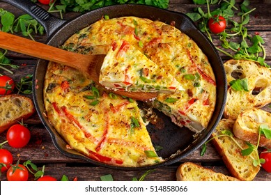 Frittata made of eggs, potato, bacon, paprika, parsley, green peas, onion, cheese in iron pan. on wooden table.