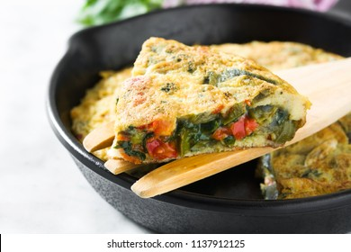 Frittata made of eggs and vegetables in a iron pan, on white marble