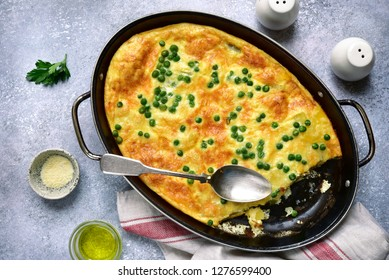 Frittata with potato, cheese and green pea in a skillet over light grey slate, stone or concrete background.Top view.
