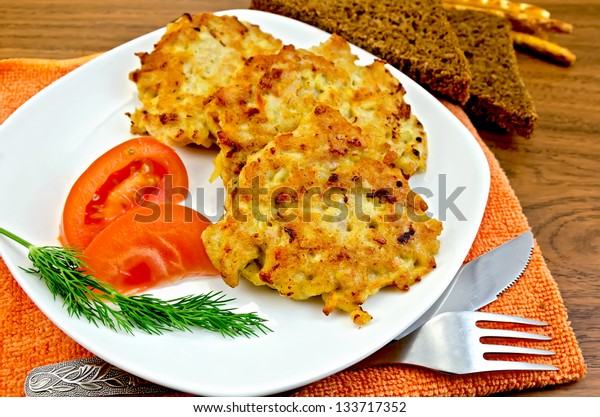 Fritters of minced chicken on a white plate with tomato and dill, knife, fork, napkin orange, rye bread on a wooden board