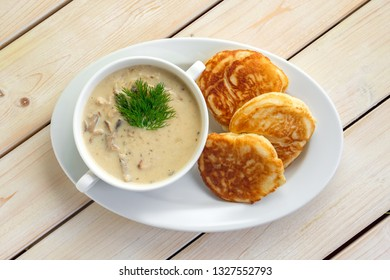 Fritters with mushroom sauce. Traditional Slavic pancakes with fat mushroom and flour sauce.