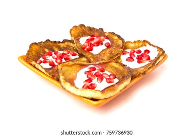 Fritters on a white background on a plate. Pancakes on an orange plate with sour cream, jam and pomegranate.