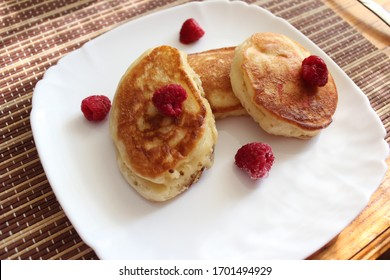 fritters on a white plate with raspberries