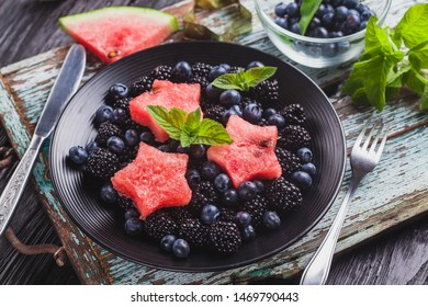 Frock blueberry, blackberry, watermelon and mint salad on an old wooden table. healthy food