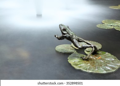 A frog jumps into water. A metal jumping frog sculpture. Long exposure.