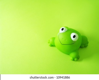 a frog toy on a green background
