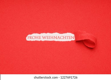 Frohe Weihnachten is German for merry christmas - xmas greeting seen through hole peeled in red paper background