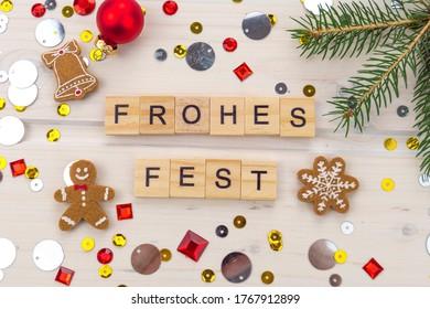 Frohes Fest mit Tannenzweig, Sternen und Weihnachtsbaum Dekoration, German Frohes Fest with Decoration on a wooden background