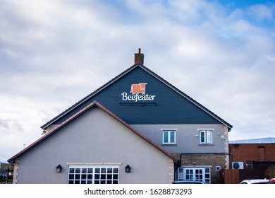Frome Somerset UK January 17 2020 The beefeater logo and text on the end of the Frome Flyer restaurant building against a cloudy sky with areas of blue