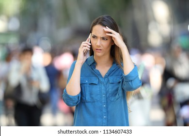 Fronf view of a worried woman talks on the phone walking in the street