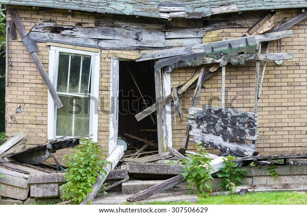 Front of an abandoned house that is falling down