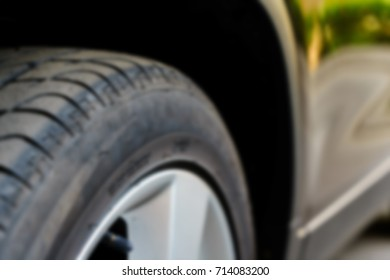 The front arches and wheels of the car blurred abstract background
