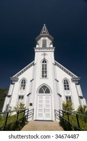 Front architectural view of a classical white wooden church.