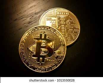 Front and back of golden bitcoins, the cryptocurrency on a dark wooden table