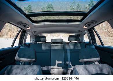 Front to back inside view in luxurious modern car. Panoramic double sunroof, blue sky, open space. Leather interior upholstery, car passenger and driver seats, clean, angle view side
