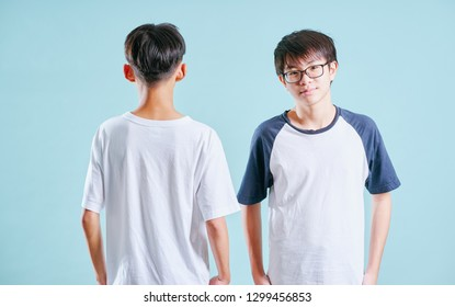 Front and back view of young asian teenage boy isolated on blue background .