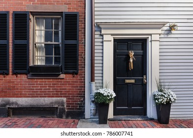 Front black door with a brick wall and black shutters outlining the window