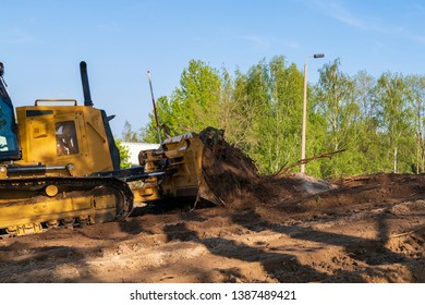 In front of the blade of a bulldozer topsoil and roots pile up