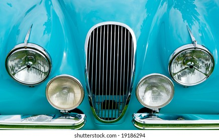 Front of blue classic car showing grill, headlights and fender.