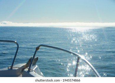 Front of boat whit sunlight reflecting in glittering sea. Sparkling in water - background. Sea water with sun glare and ripple. Powerful and peaceful nature concept.