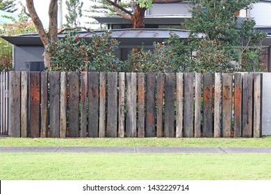 Front boundary fence made of vertically placed old railway sleepers