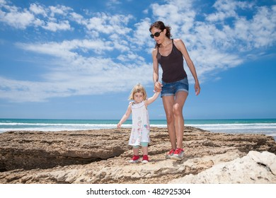 front brunette woman black shirt blue jeans shorts holding hand of two years old blonde child walking on rocks next to sea shore in Cadiz Andalusia Spain