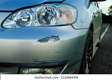 The front bumper of a car with scratches from the accident.