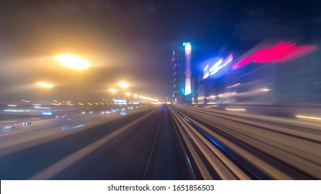 Front cabin POV view from modern driver-less metro train rush forward, along night Dubai, smooth timelapse. Overground railway, dark low rise buildings around, bright road lights at night. Motion from