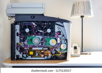 Front close up inside of a office copier machine. Electronic parts and fans. Standing on a desk with a talbe lamp.