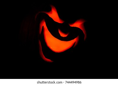 Front close up view of angry jack-o-lantern face lit up by candle and pumpkin blacked out glowing red evil smile