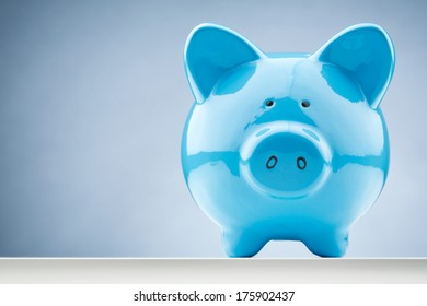 Front closeup image of a blue piggy bank with copy space.