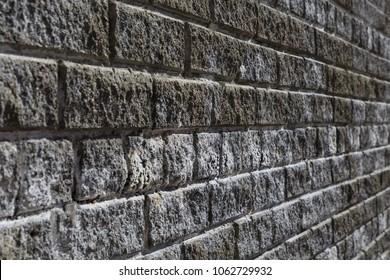 Front close-up view of a brick vintage wall at a 45 degree angle. Bricks are grey and white.