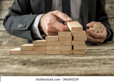 Front closeup view of businessman constructing steps of wooden pegs with focus to the peg in his hand, shallow dof.