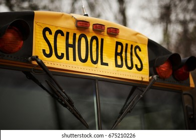 Front closeup view of yellow school bus windshield sign and lights