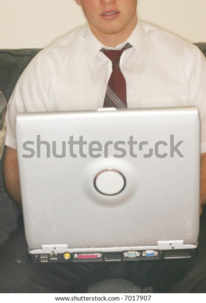 front close-up view of young man with loose tie holding laptop on knees as he sits on sofa