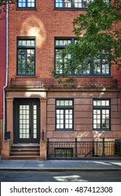 The front of a colorful brownstone home.