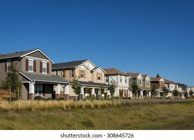 A front corner view of a row of colorful new houses.
