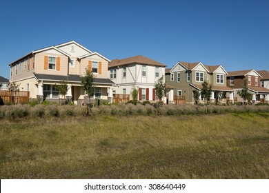 A front corner view of a row of new houses.